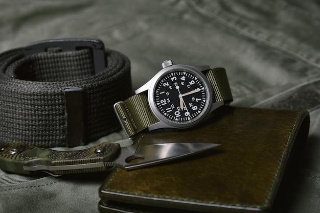 육군 녹색 배경, 클래식 시계 기계식 손목 시계, 군사 남성 패션 및 액세서리에 나토 스트랩과 전술 나이프가있는 빈티지 군사 시계.