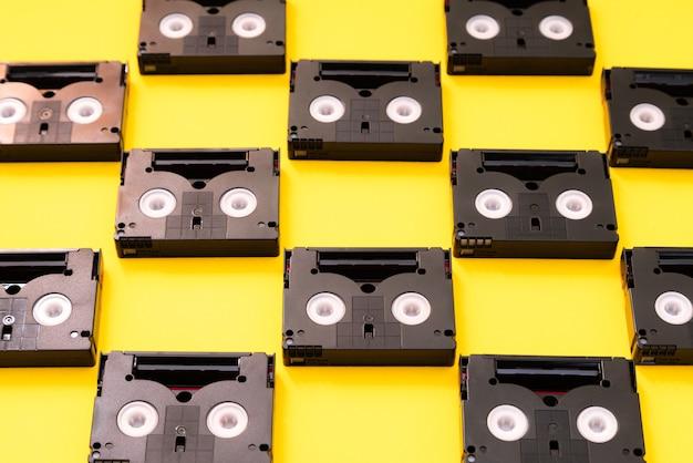 옛날에 촬영에 사용했던 빈티지 미니 dv 카세트 테이프. 노란색 배경에 플라스틱 비디오 테이프로 만든 패턴