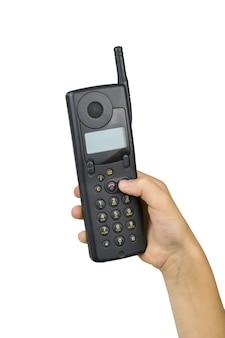 흰색 표면에 고립 된 아기의 오른손에 빈티지 휴대 전화. 레트로 커뮤니케이션 수단. 과거의 기술.