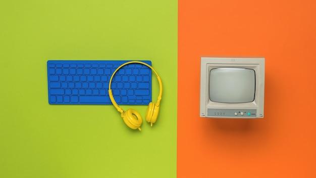 오렌지 배경에 빈티지 모니터와 파란색 키보드. 레트로 장비입니다. 플랫 레이.