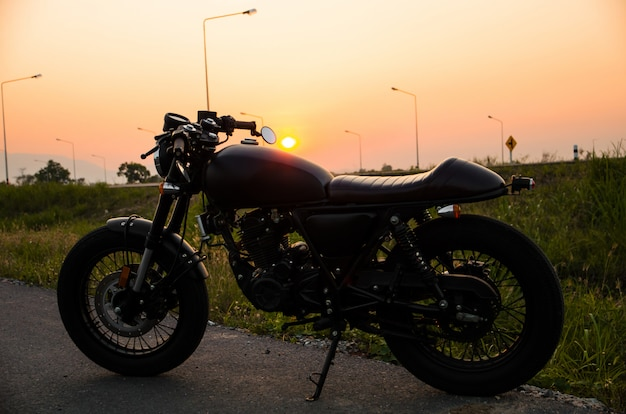 Vintage motorcycle cafe racer style with sunset scene