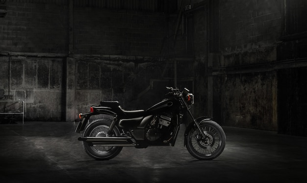 Винтажный мотоцикл, стоящий в темном здании в лучах солнечного света. вид сбоку
