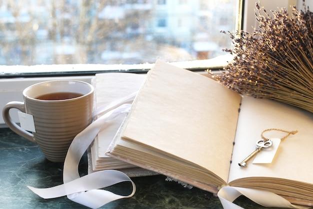 Винтажная записная книжка на зеленом мраморном подоконнике, открытая пустыми страницами и букетом лаванды