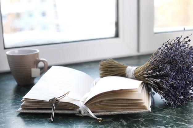 空白のページとラベンダーの束で開いた緑の大理石の窓辺のヴィンテージノートブック