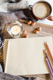 Vintage notebook with pencils, candle and coffee