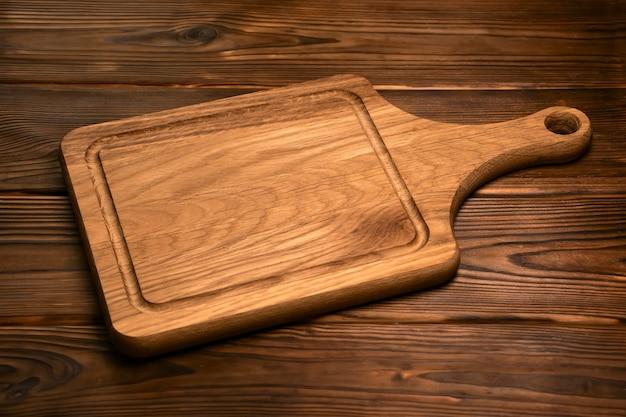 Винтажная дубовая разделочная доска на старой деревянной поверхности