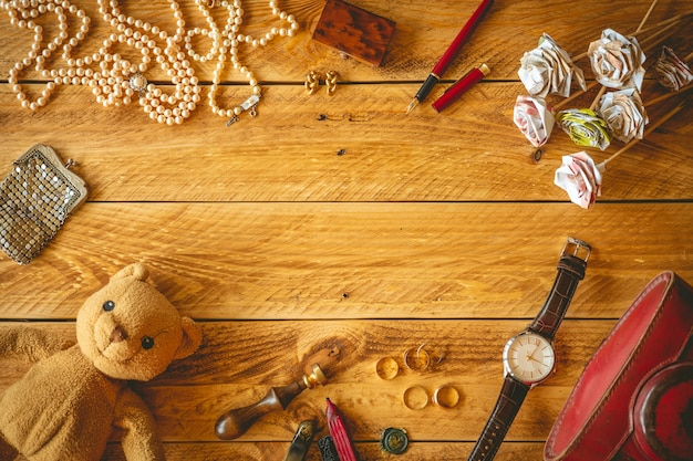Vintage objects and jewelry in a wooden table with copy space in the middle.
