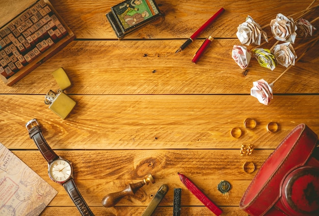Vintage objects in a wooden table with copy space in the middle.