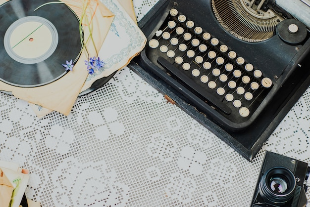 Vintage office desk with typewriter, stack of vinyl and camera on tablecloth