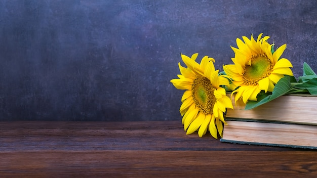 Vintage old books and bouquet of sunflowers