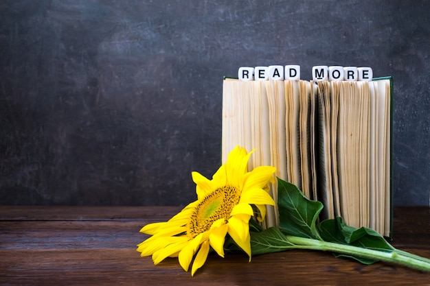 Vintage old books with words read more and sunflower