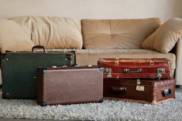 Vintage old classic outdated leather suitcases in interior of bright room by sofa