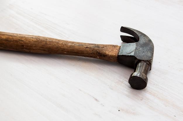 Vintage old hammer tool on the wood floor background