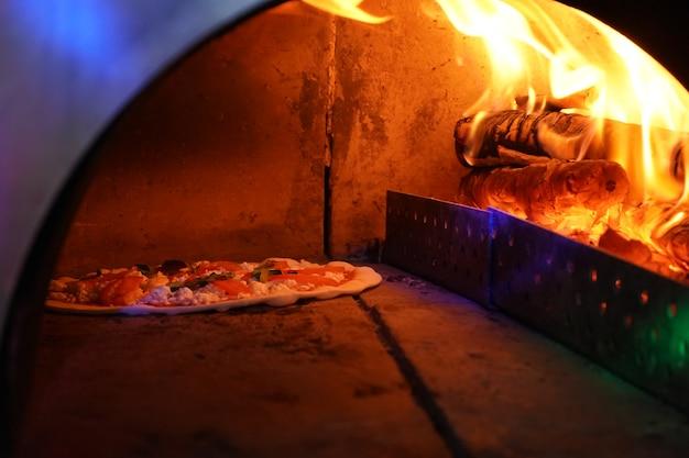 Винтажная старая духовка с огнем внутри для выпечки оригинальной пиццы.