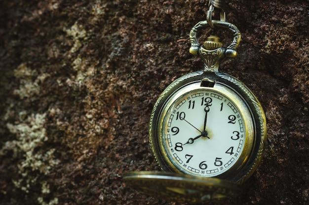 岩の上にぶら下がっているヴィンテージの古い懐中時計
