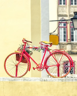 Vintage old red bicycle decorated with flowers and a basket.