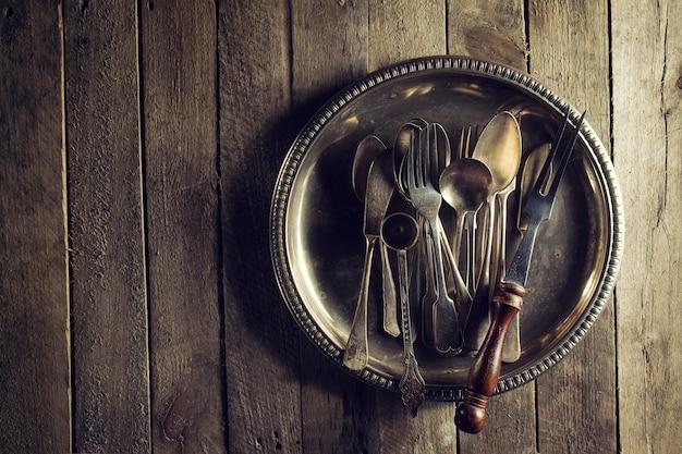 빈티지 오래 된 소박한 주방 용품 포크 숟가락과 오래 된 나무 테이블에 나이프. 음식이 나 빈티지 소박한 개념. 평면도.