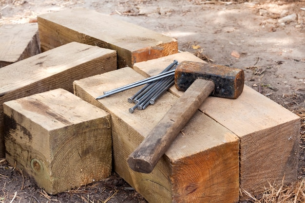 Vintage old rusty hammer and nails lying on wooden bars