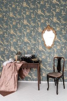 복고풍 테이블에 빈티지 올드 스타일 타자기. 오래된 가구와 벽에 vintege 거울이있는 복고풍 인테리어.