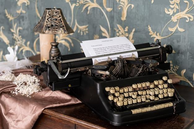 Винтажная пишущая машинка старого стиля на ретро таблице. ретро-интерьер со старой мебелью и винтежным зеркалом на стене.