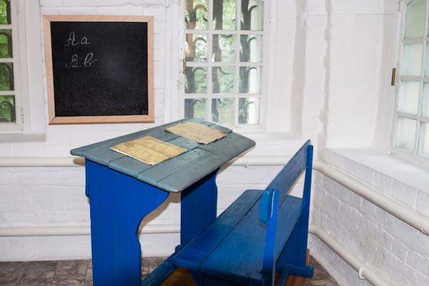 古いマナースクールの青い色のヴィンテージの古い木製の学校の机