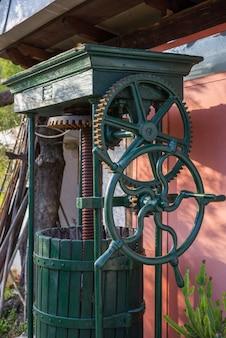 Vintage olive press with wooden barrel, close up