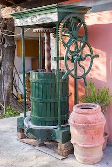 Vintage olive press with wooden barrel terracotta jar