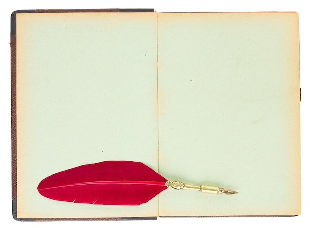 Vintage open book with red feather pen isolated on white