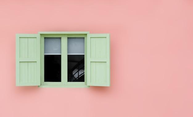 ヴィンテージオープングリーンミントシャッターとピンクで分離された木製の窓