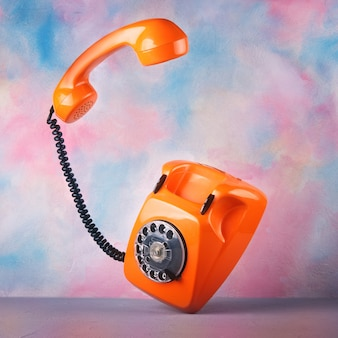 Vintage orange telephone on a bright watercolor