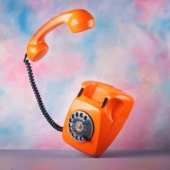 Старинный оранжевый телефон на яркой акварели