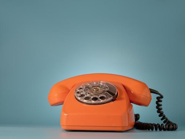 Старинный оранжевый телефон на синей стене