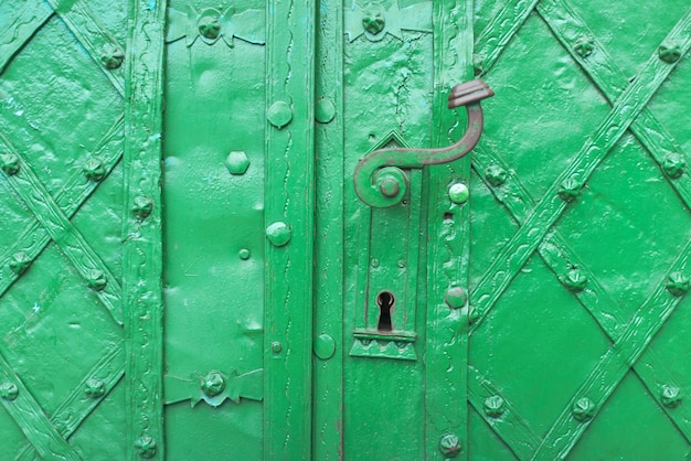 Vintage ornament of green color, part of the iron door of medieval castle