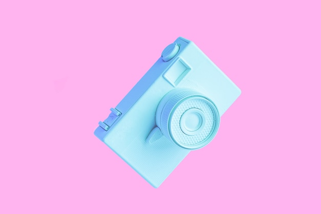 Vintage painted blue camera against pink background