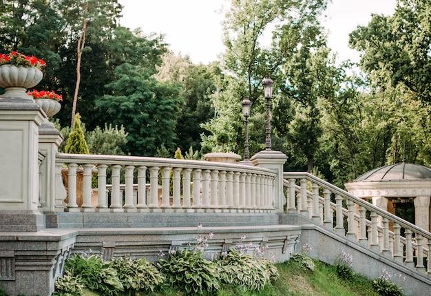 手すりと手すりの階段と植木鉢のある柱のあるヴィンテージの宮殿の柵