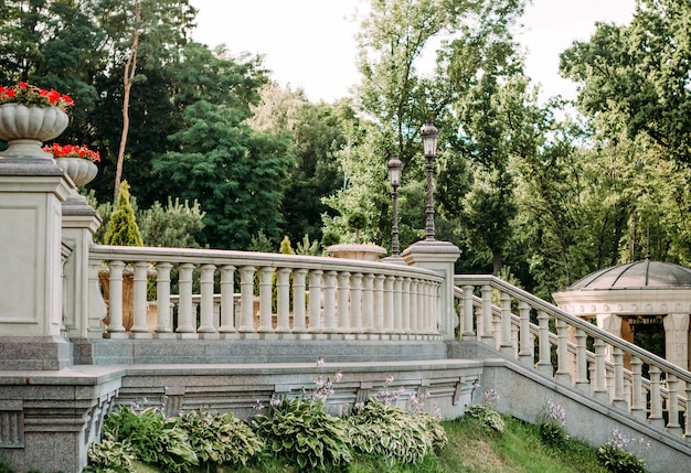 Vintage palace fence with balustrades and handrails steps and columns with flowerpots