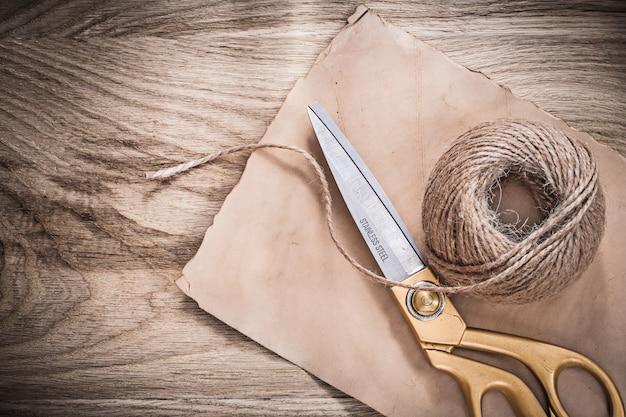 Vintage paper golden scissors hank of rope on wooden board