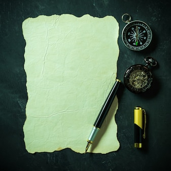 Vintage paper and pen with compass and pocket watch on black background.