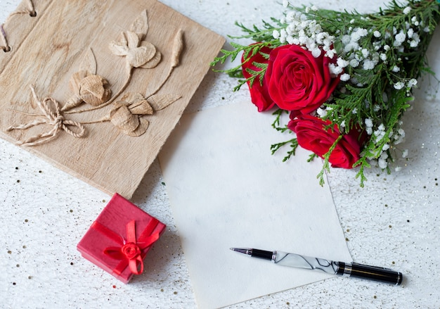 Vintage paper and pen to write with gift and roses Premium Photo