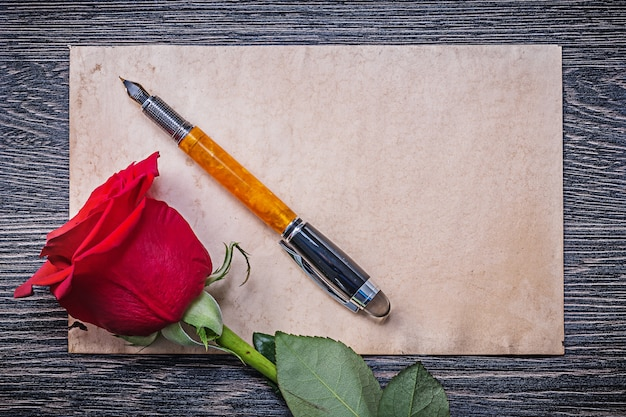 Vintage paper red rosebud fountain pen on wooden board