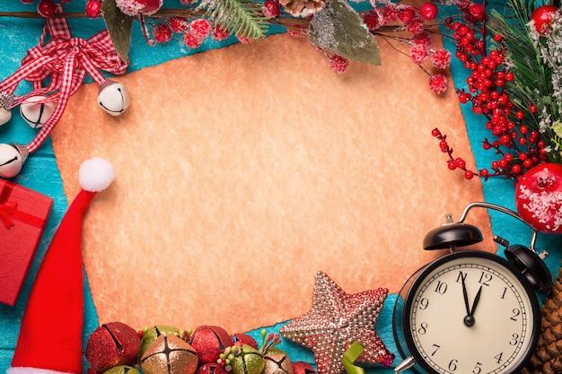 ヴィンテージ紙、サンタの帽子、時計、青い木製のテーブルの装飾。フラットレイ