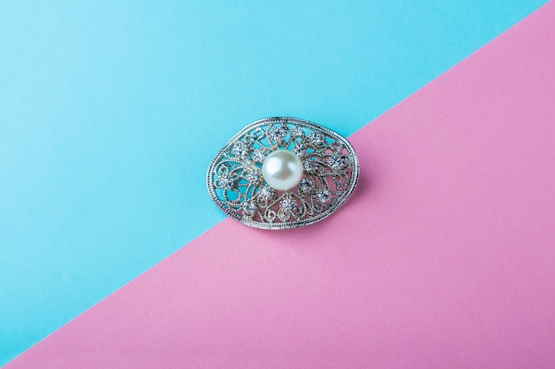 Vintage pearl jewelry brooch on pink blue background. elegant gift for woman.