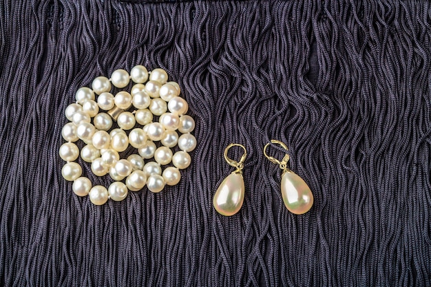 Vintage pearl jewelry on little black dress. gatsby or chicago fashion look. luxury white necklace and earrings. getting ready for party.