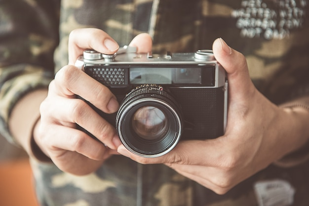 Vintage photo camera in the hands of man, soft focus.