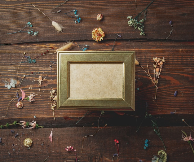 Vintage photo frame next to dry herbs on wooden table