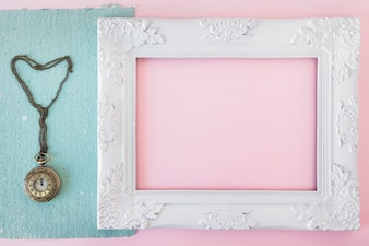 Vintage photo frame near blue paper and old pocket watch