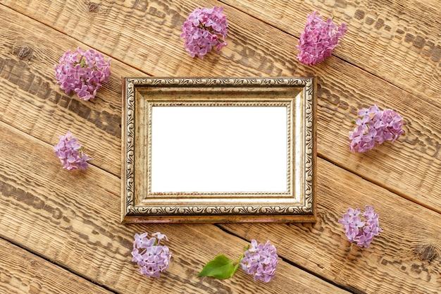 古い木の板にコピースペースとライラックの花とヴィンテージのフォトフレーム。上面図。