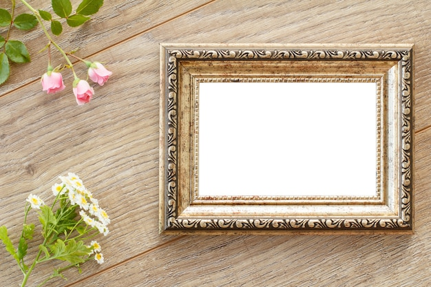 Vintage photo frame with copy space and flowers on wooden boards. top view.