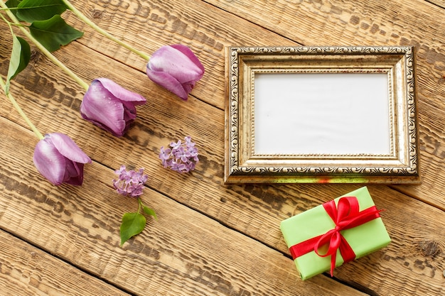 Vintage photo frame with copy space, lilac tulips and gift box on old wooden boards. top view.