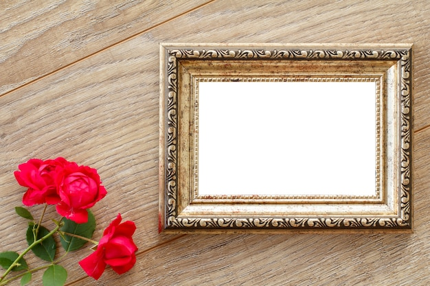 Vintage photo frame with copy space and red roses on wooden boards. top view.